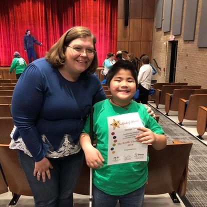Tracy Fitch standing with a boy holding a Braille Challenge certificate