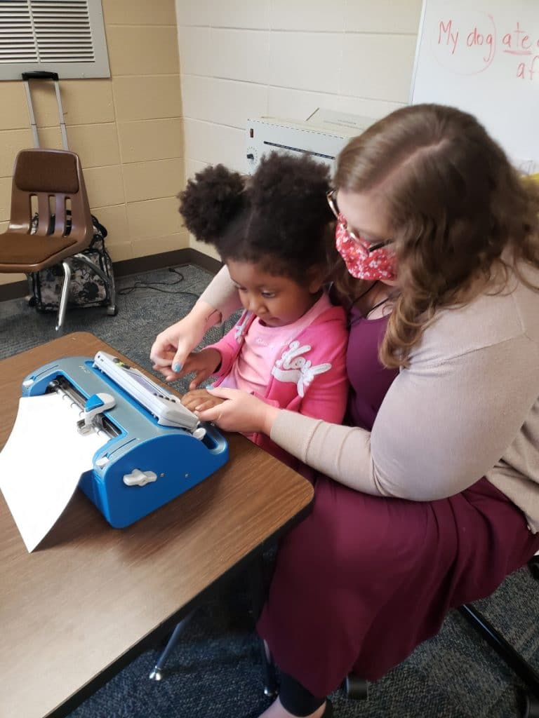 Tracy Fitch sitting with a girl and a braille typewriter