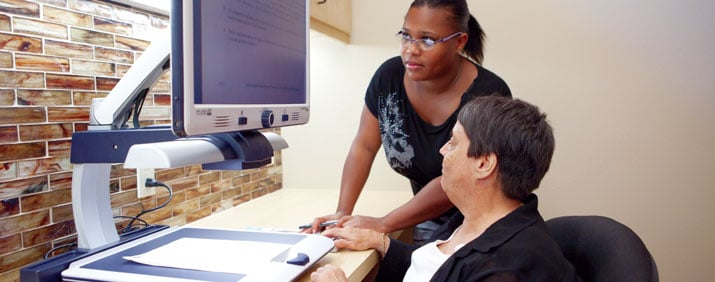 Braille Institute Employee helping a woman with assistive technology