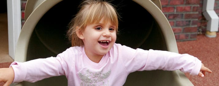 A visually impaired child slides down a slide with a big smile on her face.