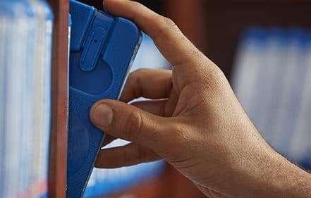 A hand on a cartridge on the bookshelf