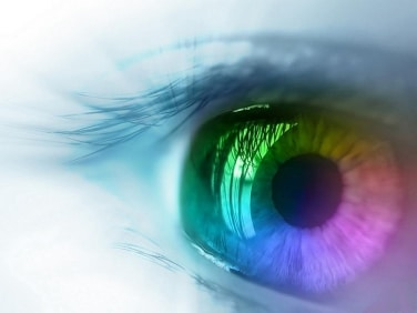 Close-up of an eye reflecting various colors