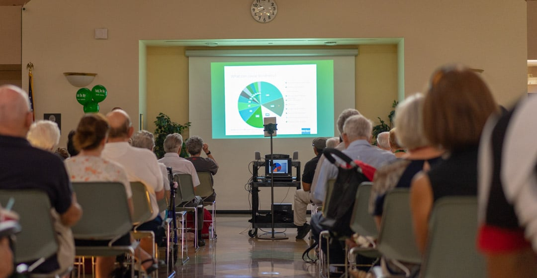 An audience looking toward a pie chart on a presentation screen