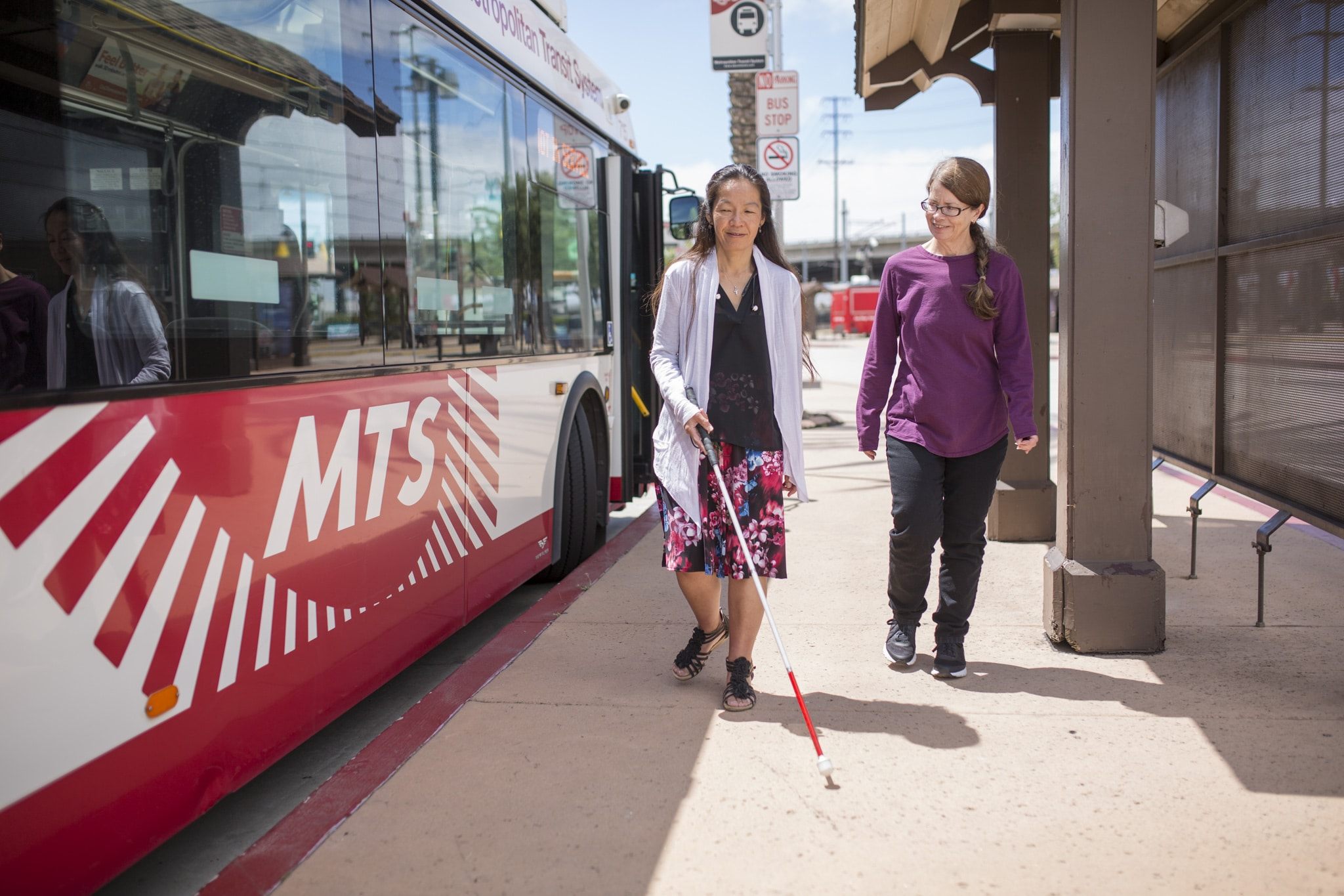 Braille Institute Orientation and Mobility Specialist Keema McClung walks with a woman with a white cane