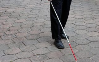 The legs of someone holding a white cane