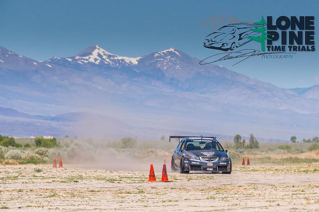 Race car driving around cones with mountains in background