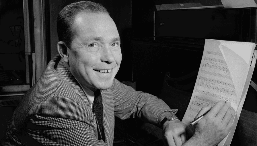 Johnny Mercer smiles at the camera with pencil in hand over a sheet of music