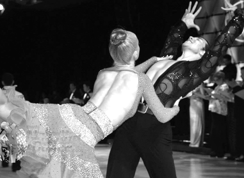 Black and white image of a man and a woman dancing wearing elaborate costumes