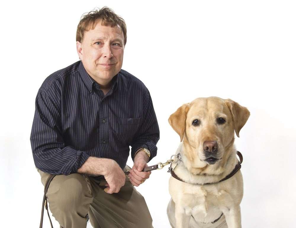 Book author Stephen Kuusisto poses for a photo alongside his guide dog