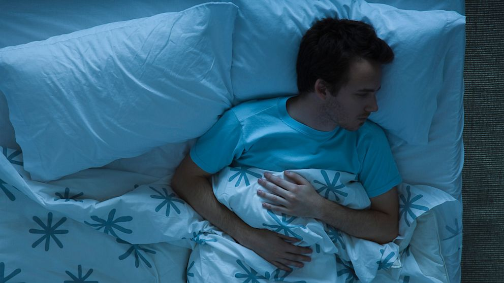 A young man lies awake in bed