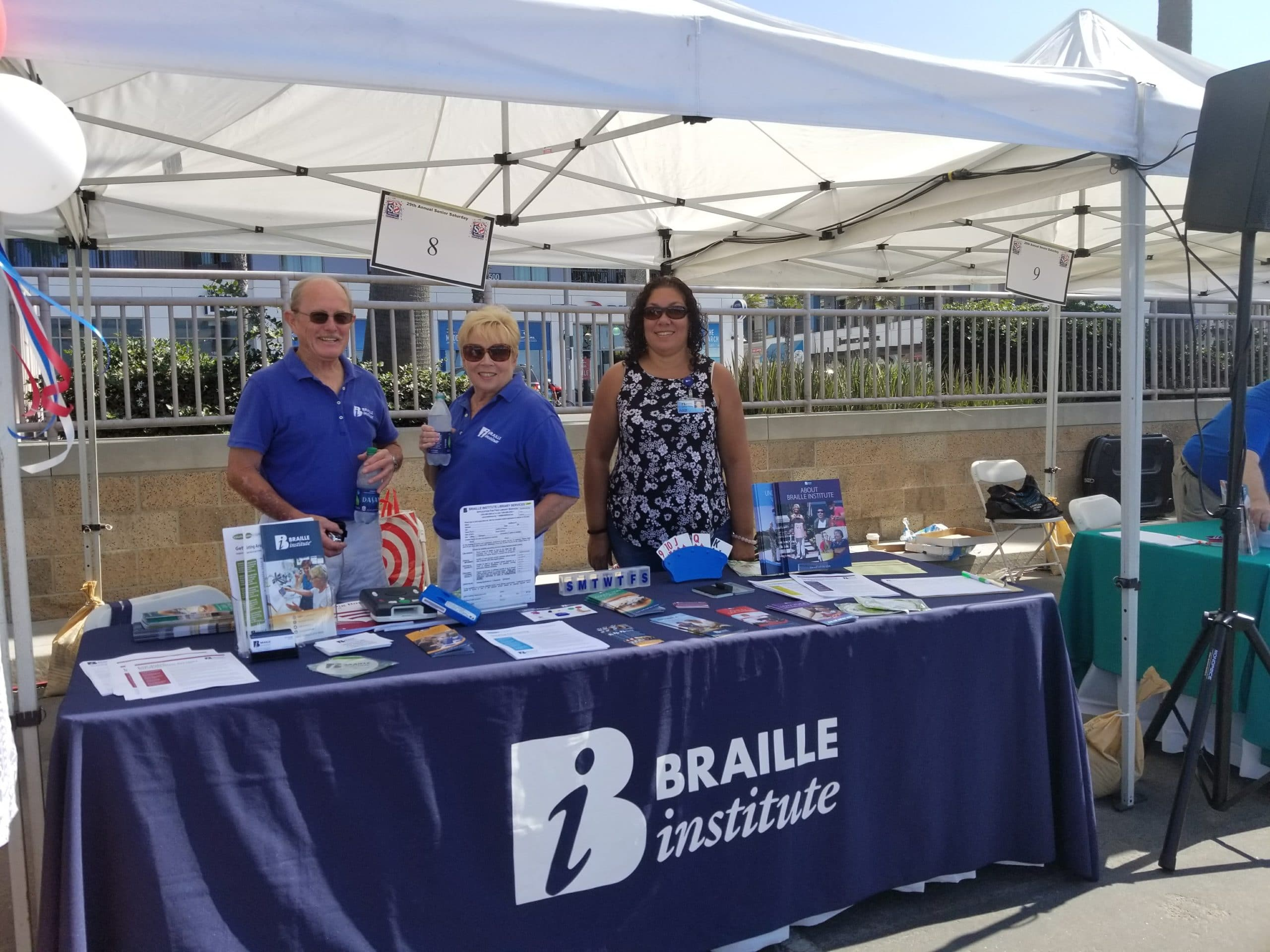Three Braille Institute staff and volunteers standing at a booth at an outside event