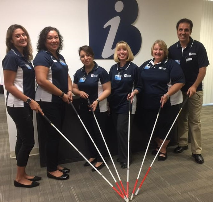 Six Braille Institute staff holding the tip of white canes together