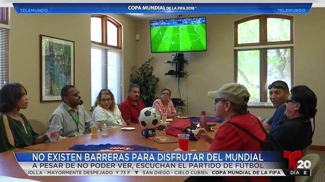 Students sit around a table listening to the World Cup soccer game on a big screen TV.
