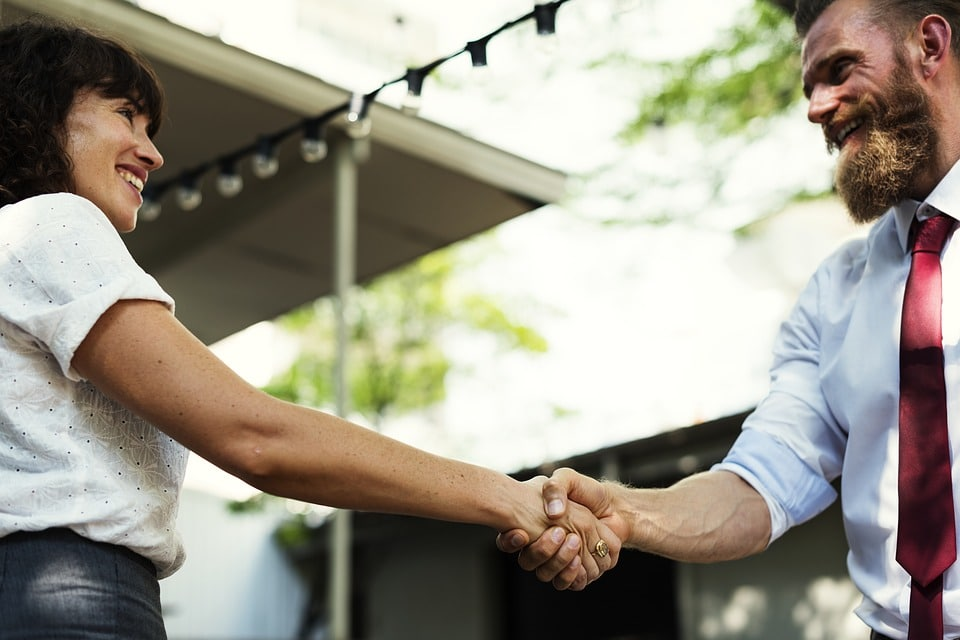 Woman on left is shaking hands with man on right