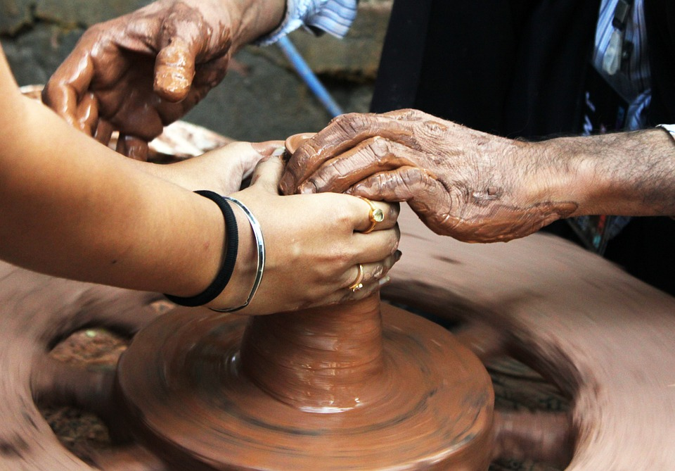 Young woman helps man form clay on a wheel
