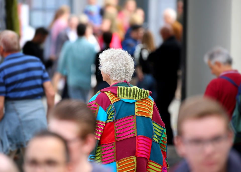 Elderly woman in multi color coat stands out in a crowd.