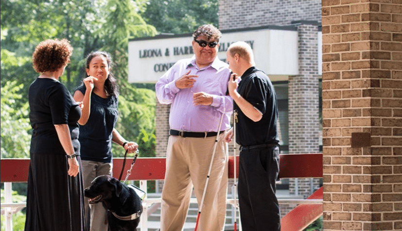 Four people with a guide dog and several canes stand outside a building and talk