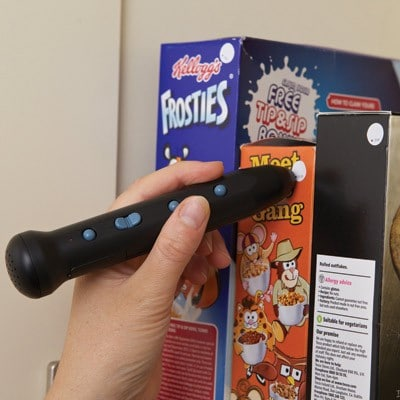 A hand holding a pen device up to a row of cereal boxes