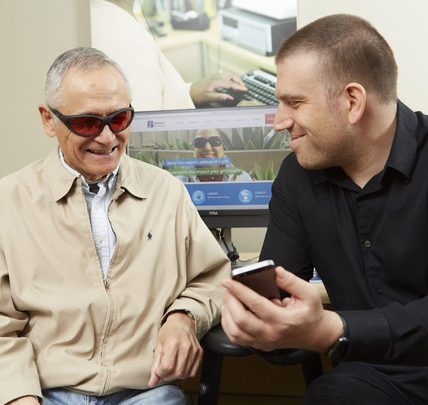 A man showing an older man something on a smartphone
