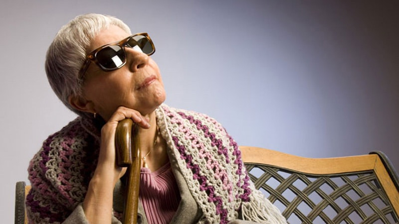 An older woman wearing sunglasses holds a cane while sitting in a chair