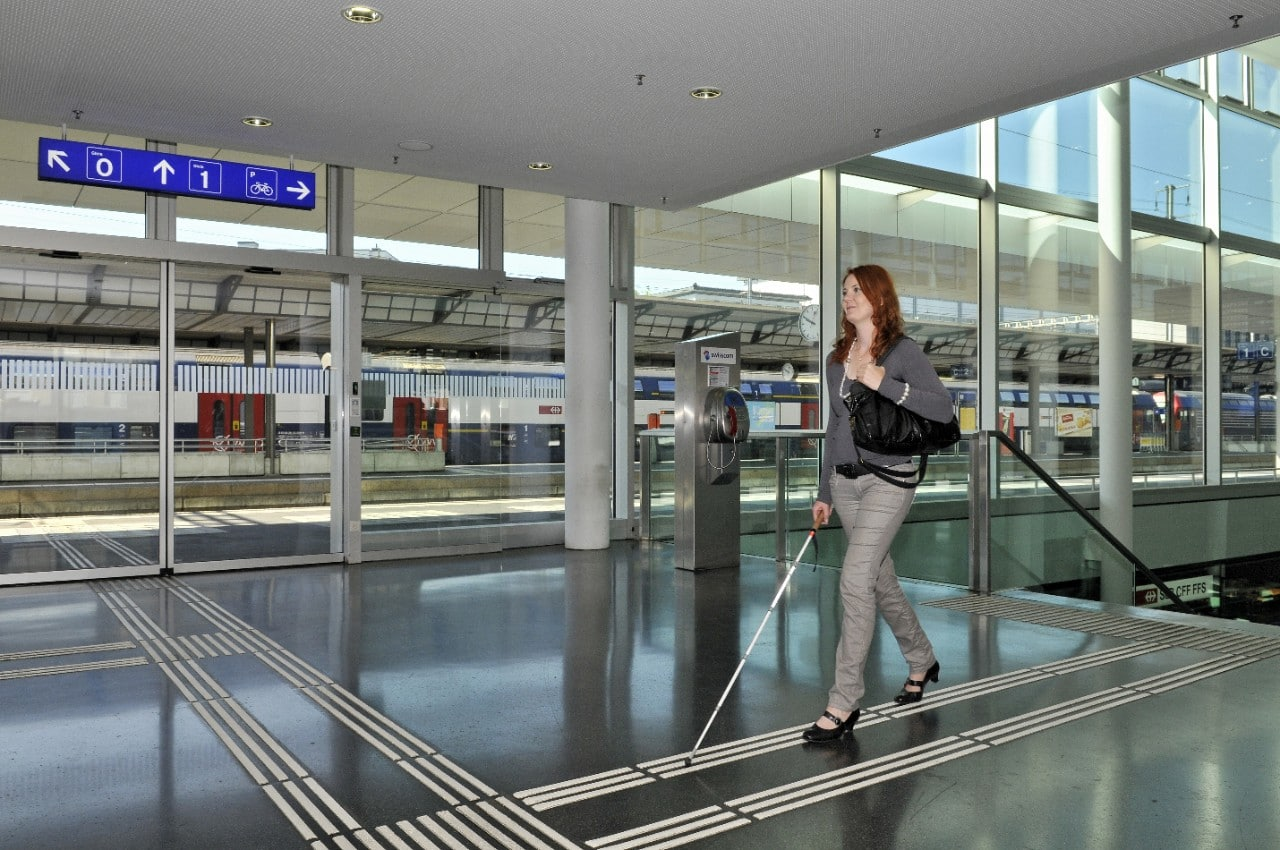 A woman with a white cane walking through a train station