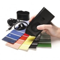 A hand holding a device over four color swatches