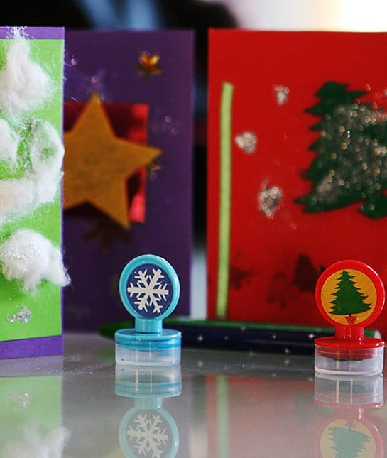A snow flake stamp and a Christmas tree stamp, and in the background are holiday-themed boxes or cards
