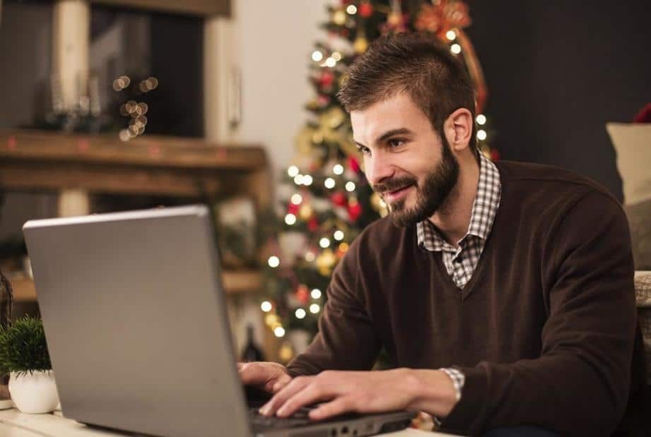 A smiling man at a computer laptop. In the background is a Christmas tree.