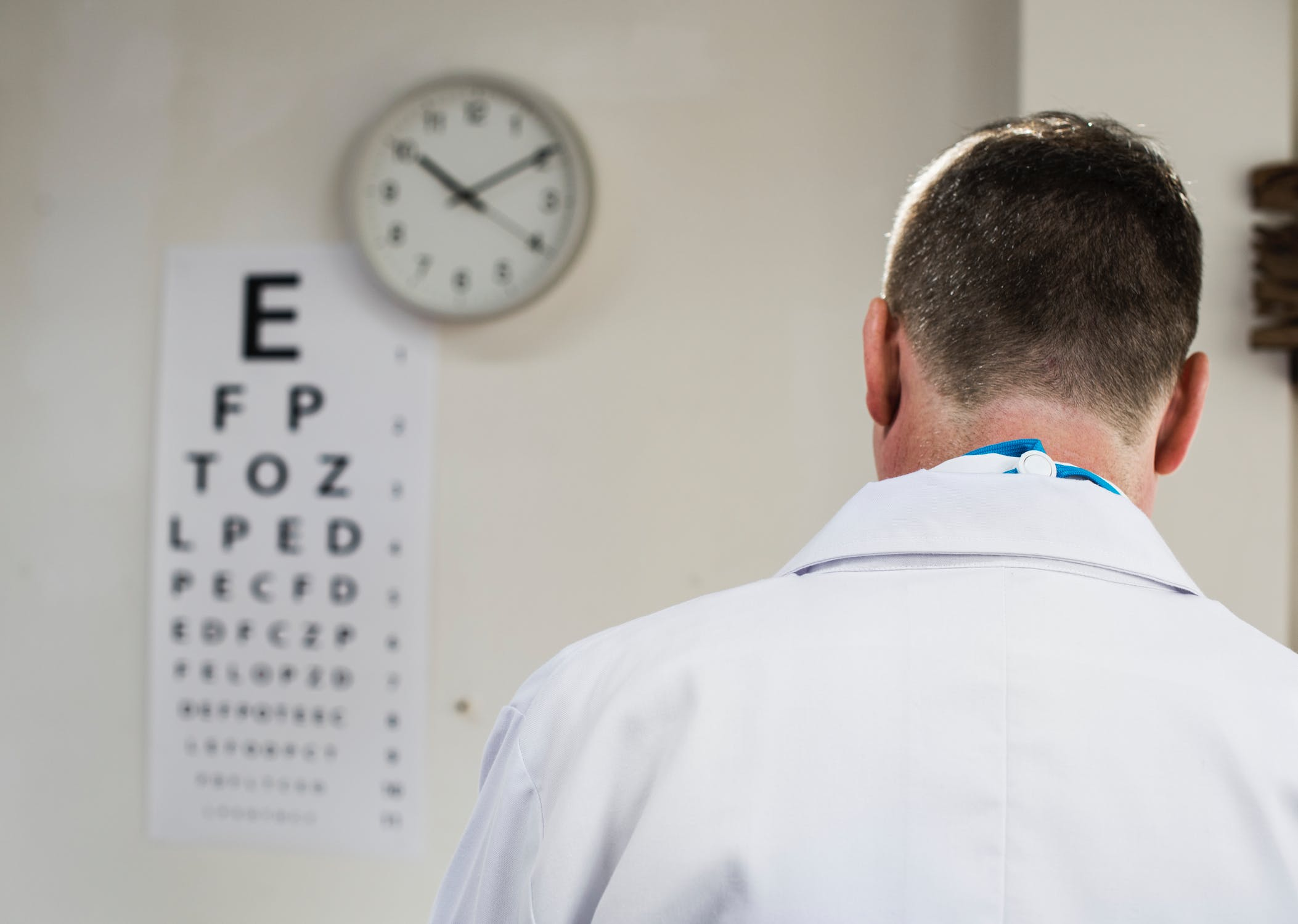 A doctor stands in the foreground with eye chart and clock on the wall in the background