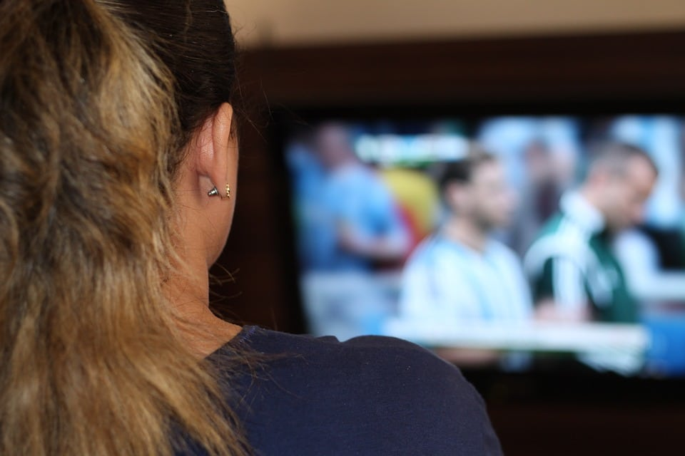 The back of a woman's head, a television in the distance