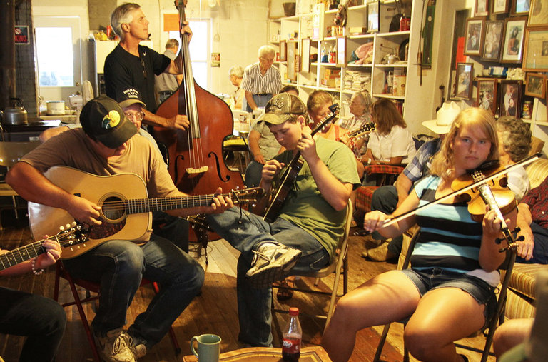 Adults and youth playing different string instruments