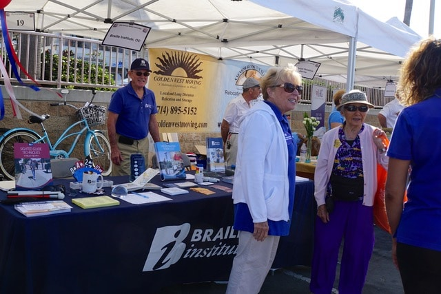 Several people talk in front of a Braille Institute booth at an event