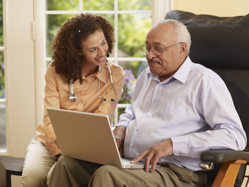 A woman with a stethoscope sitting next to an older man on a laptop