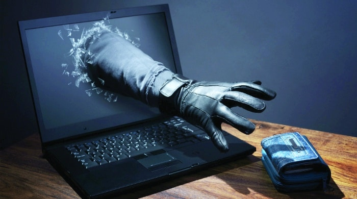A gloved hand reaching out of a computer screen toward a wallet on the table