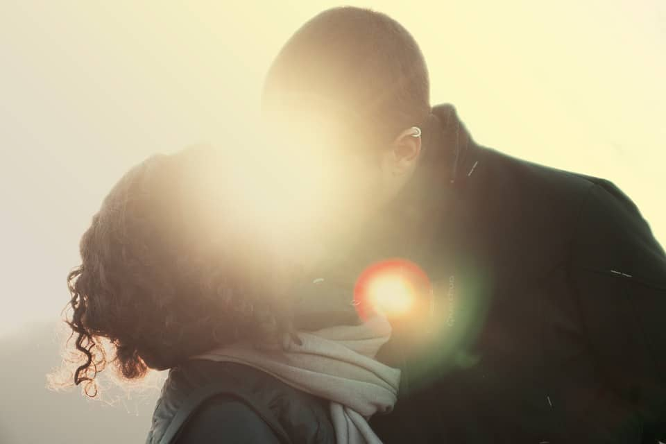 Man and woman kissing, but the sun is directly behind them glaring out the actual kiss.