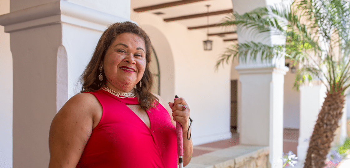 Connie R wearing a red dress, holds her white cane and smiles for the camera in a courtyard setting
