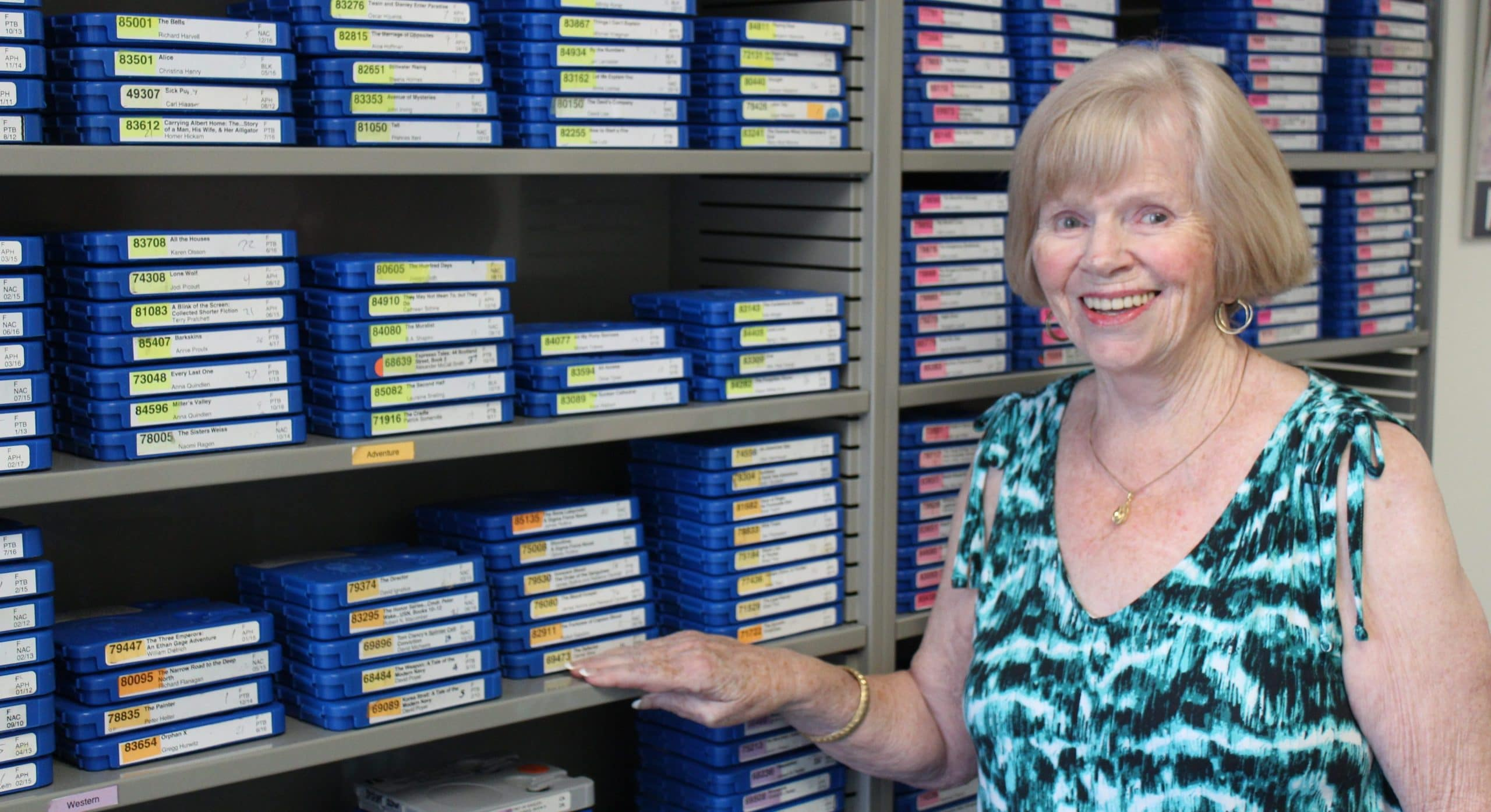 Cathy M stands infront of a bookshelf at Laguna Hills Center, her hand is resting near some audio books and she is smiling