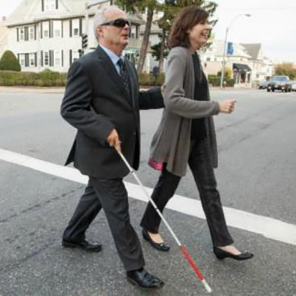 A man with a white cane holds a woman's arm as they walk across the street
