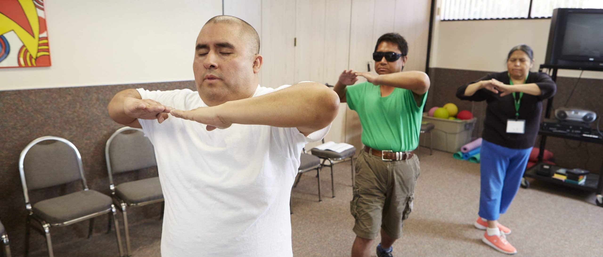 3 people with hands raised in front of their chins participating in a Tai Chi class