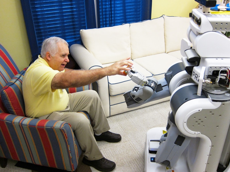 A robot hands an object to an older man sitting in a chair