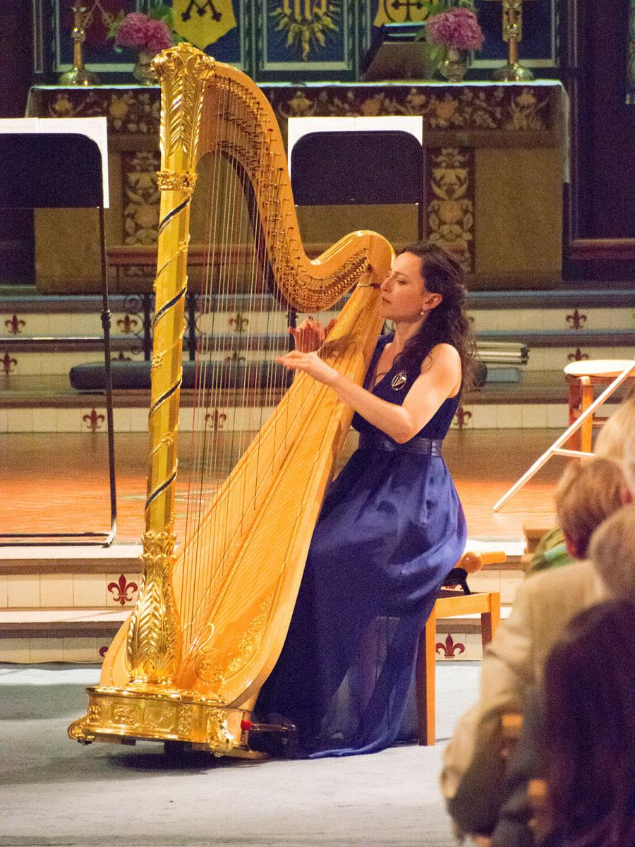 A woman playing the harp during a stage performance