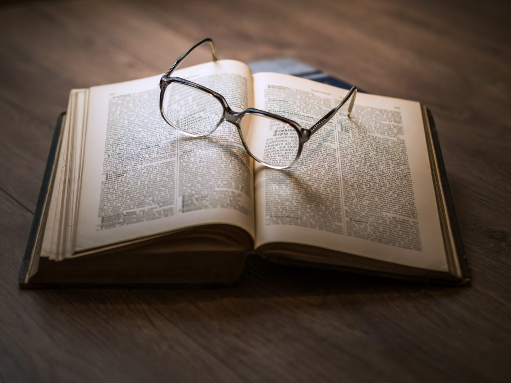 Reading glasses resting on an open book