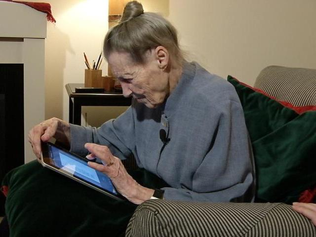 A woman sitting in an armchair uses a tablet device