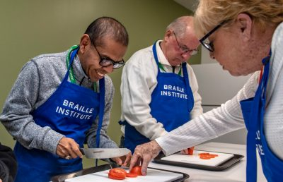 Advance cooking class volunteer Colleen Brown helps Juan Mendoza, left, and John Simon, both visually impaired, cut tomatoes at the Braille Institute in Anaheim on Tuesday, February 12, 2019. (Photo by Mindy Schauer, Orange County Register/SCNG)