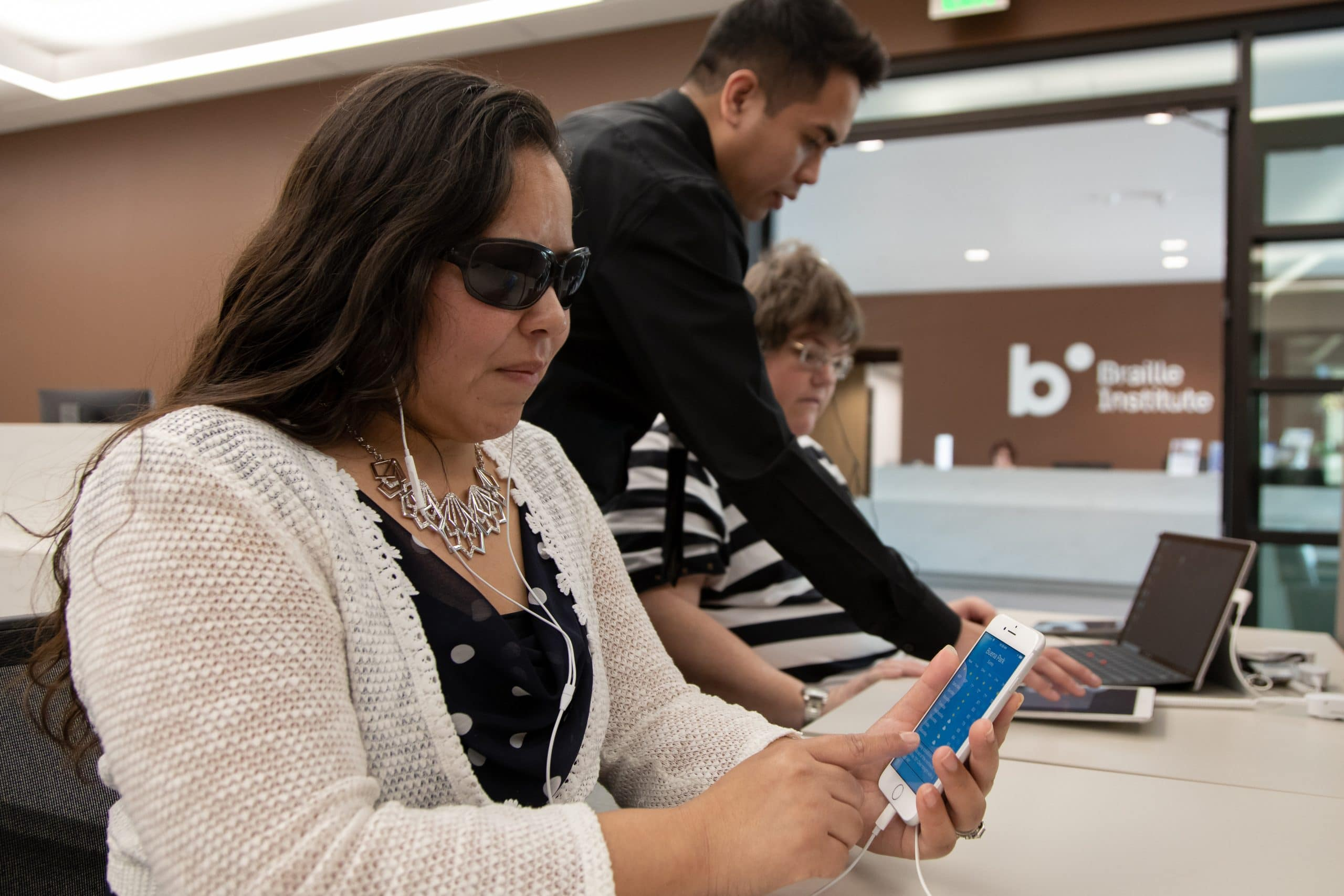 Woman using mobile device to access BARD app, instructor working with another woman in the background