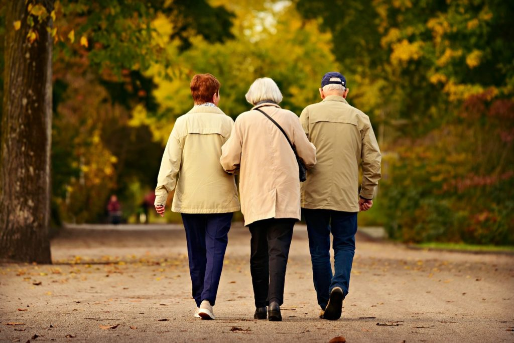 Three elderly people walking together through a park in the fall time