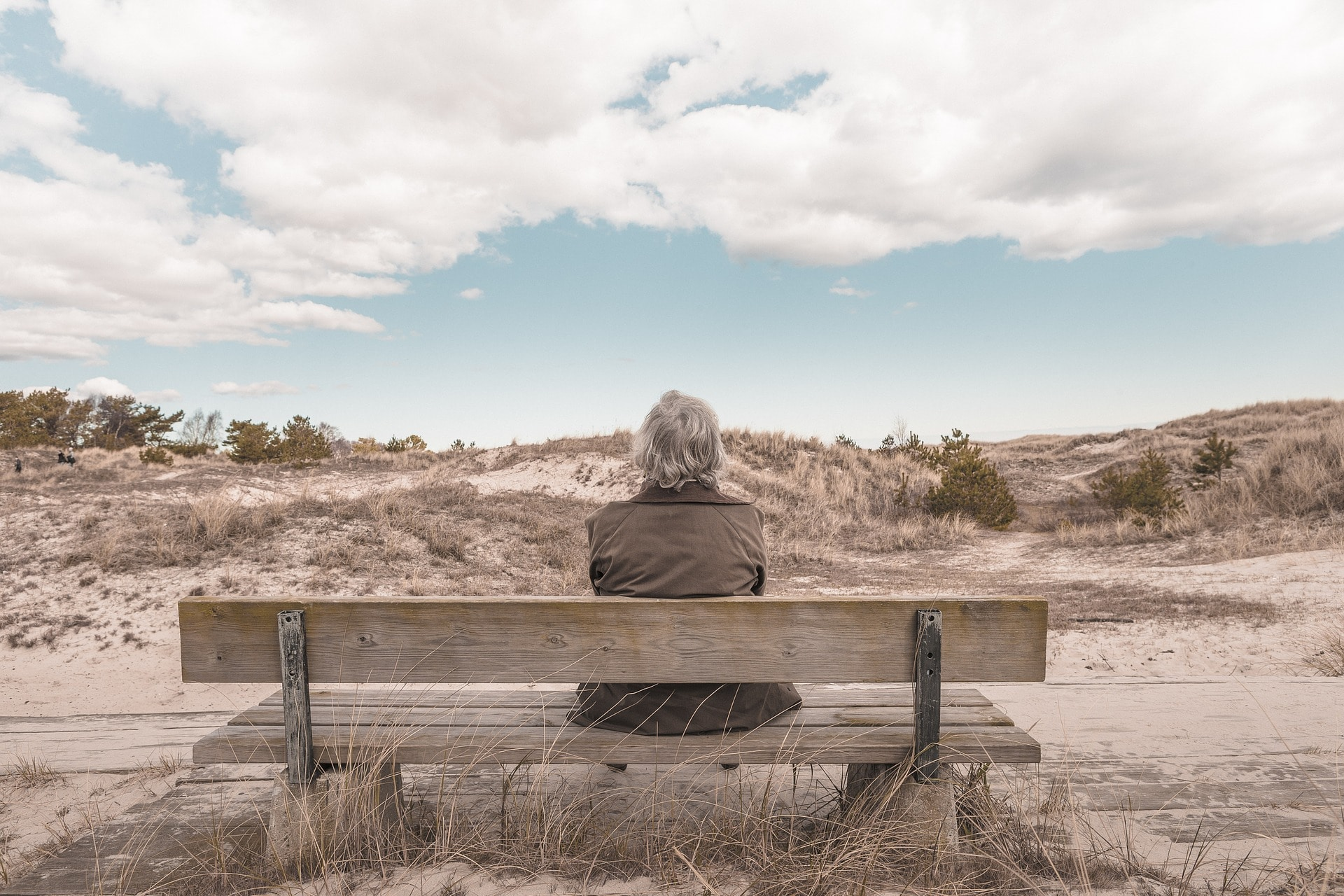 Person sitting alone on a bench looking at sand dunes