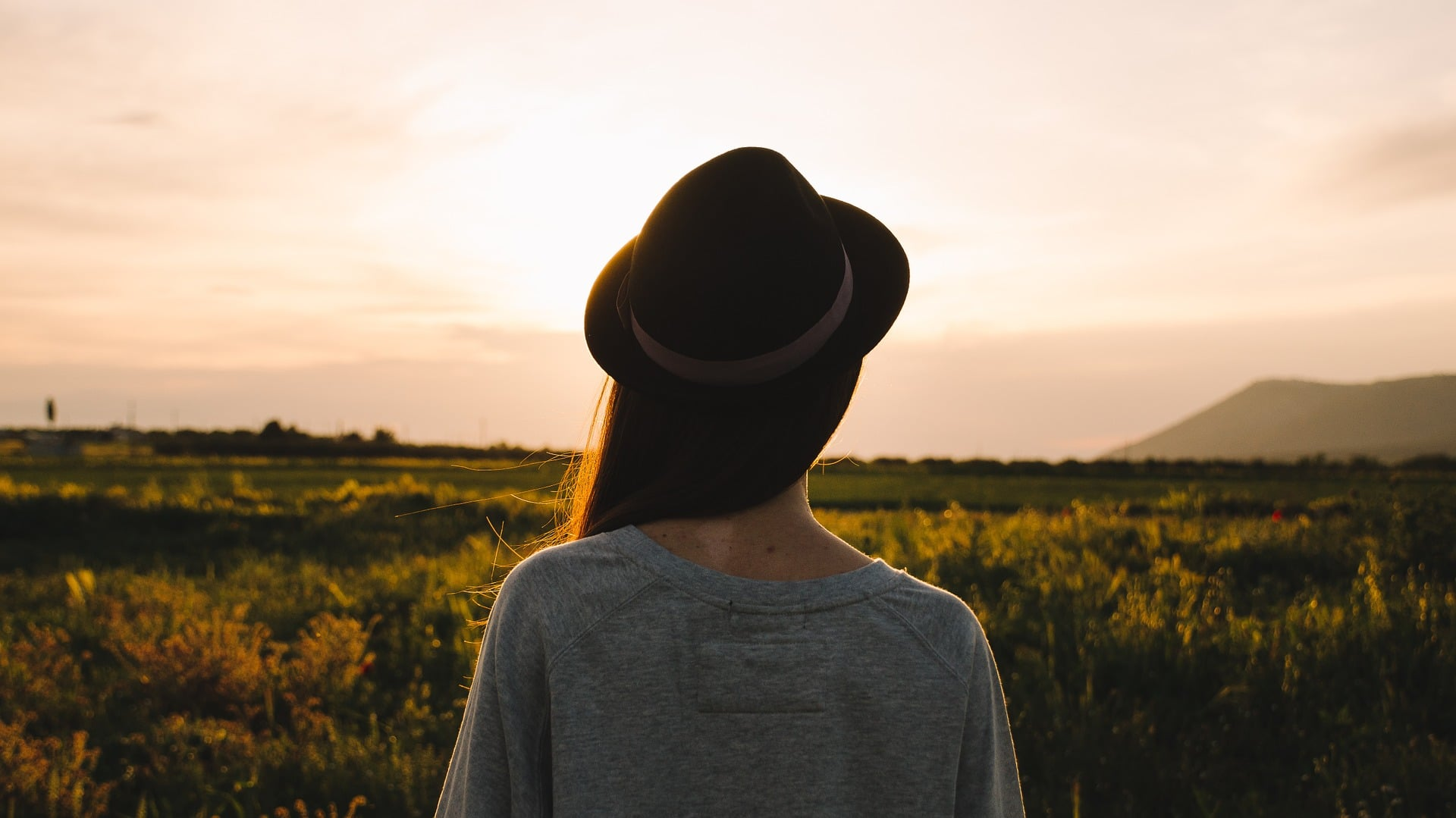 Woman wearing wide brim hat staring into sunset