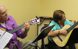 A man and a woman sitting and playing their guitars