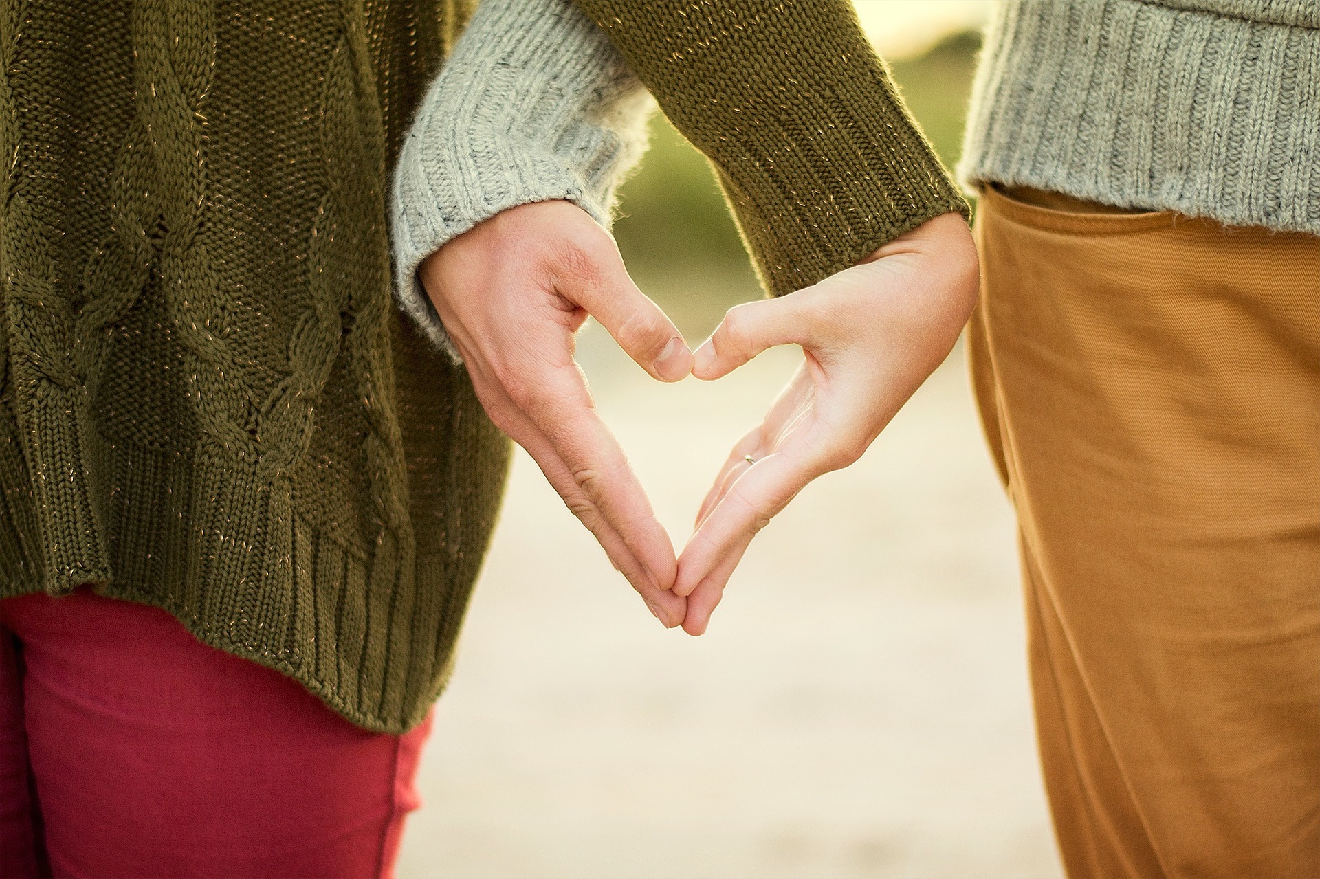 Two people putting their hands together to form a heart